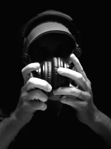 a black and white photo of hands holding large headphones