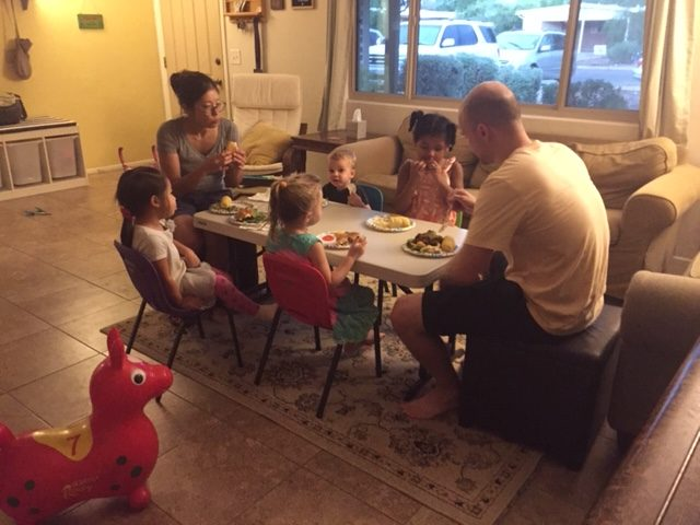 Two adults sit with four children at a small table and eat a meal.