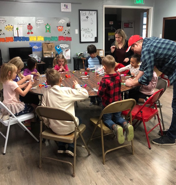 A group of young children sit at a round table and engage in a craft activity. It is the Village's Kid Vespers class.